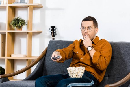 handsome man sitting on sofa, holding remote control and eating popcorn