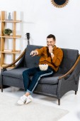 cheerful man sitting on sofa, holding remote control and eating popcorn
