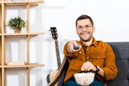 Photo pour Gai homme assis sur le canapé avec pop-corn dans un bol et détenant le contrôle à distance - image libre de droit