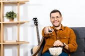 cheerful man sitting on sofa with popcorn in bowl and holding remote control