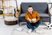 surprised man sitting on carpet with popcorn in bowl and holding remote control in living room