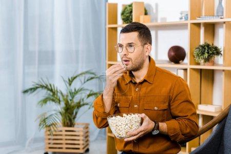 Photo pour Homme surpris dans des verres à manger pop-corn en regardant film - image libre de droit