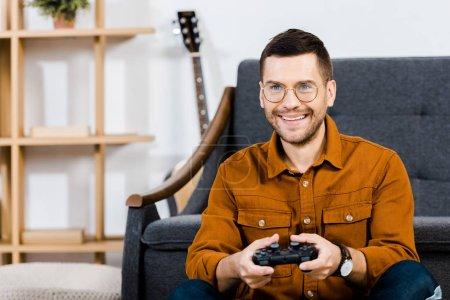 Photo pour Gai homme tenant la manette de jeu et jeu vidéo à la maison - image libre de droit