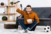 excited man holding bowl with popcorn and screaming at home