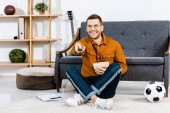 smiling man holding bowl with popcorn and remote control in hands
