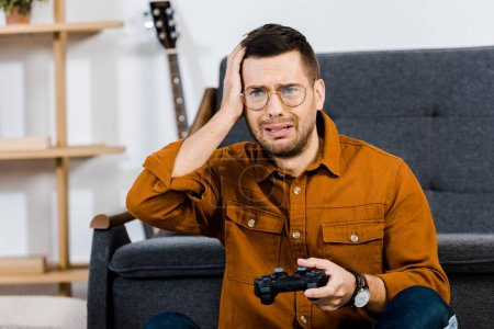 Photo for Upset man in glasses holding gamepad after playing video game - Royalty Free Image