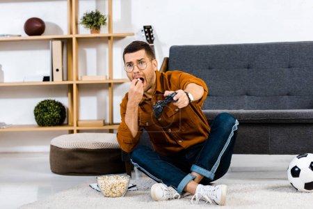 Photo pour Maïs soufflé émotionnelle homme manger tout en jouant le jeu vidéo - image libre de droit