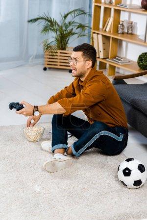 Photo pour Émotionnel homme assis sur un tapis près de pop-corn tout en jouant le jeu vidéo - image libre de droit
