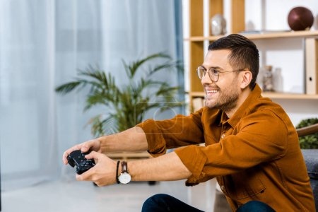 Foto de Hombre feliz en gafas jugando video juego en casa - Imagen libre de derechos