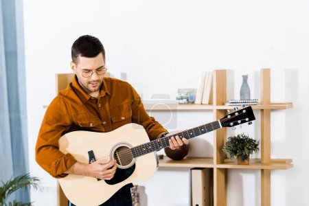Photo for Handsome musician playing acoustic guitar at home - Royalty Free Image