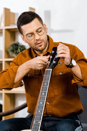 handsome man in glasses tuning acoustic guitar at home
