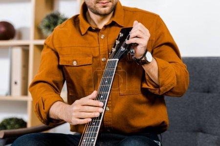Photo pour Vue recadrée de l'homme accordant la guitare acoustique à la maison - image libre de droit
