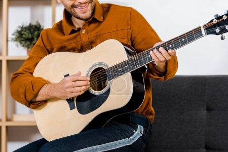 Photo pour Recadrée de l'homme gai dans des verres à jouer de la guitare acoustique à la maison - image libre de droit