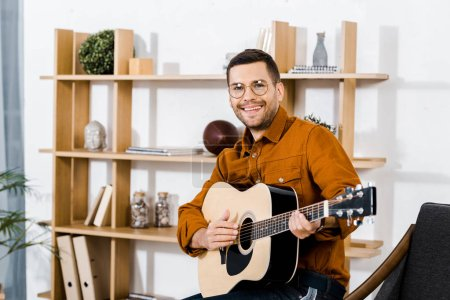 Photo for Happy man in glasses playing acoustic guitar at home - Royalty Free Image
