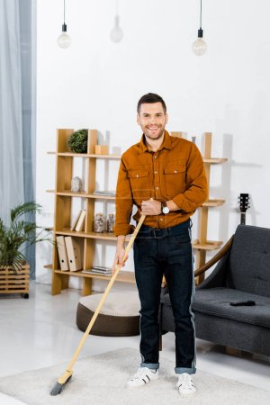 cheerful man standing with broom in modern living room