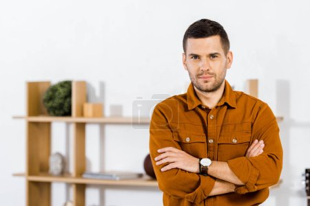 Photo for Handsome man standing with crossed arms in living room - Royalty Free Image