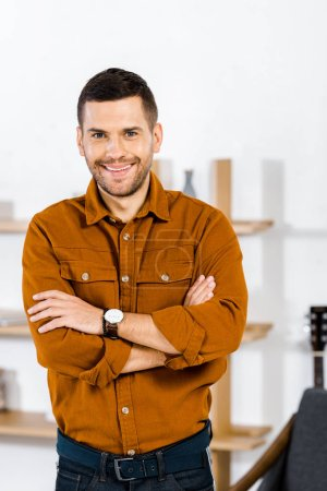 Photo for Cheerful man standing with crossed arms in living room - Royalty Free Image