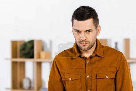 hombre molesto de pie en la sala de estar moderna y mirando a la cámara