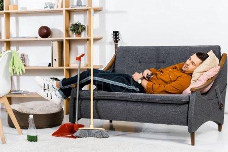 Foto de Guapo hombre durmiendo en el sofá en la sala de estar moderna - Imagen libre de derechos
