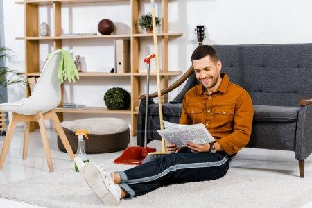 Foto de Hombre guapo sentado en suelo en la moderna sala de estar y lectura de periódico - Imagen libre de derechos