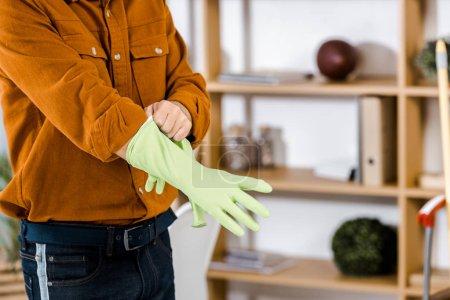 Foto de Visión recortada del hombre en la moderna sala poner guantes de goma - Imagen libre de derechos