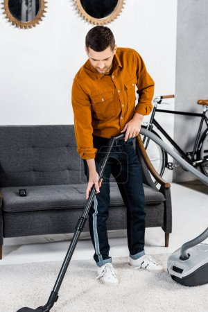 handsome man in modern living room cleaning house with hoover