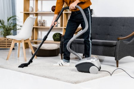 Photo for Cropped view of man in modern living room cleaning house with hoover - Royalty Free Image