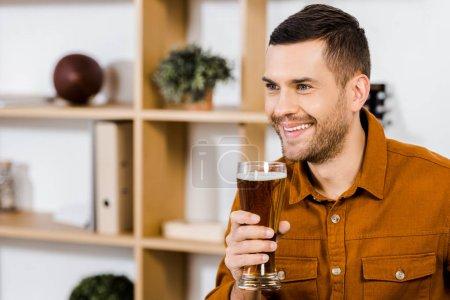 Foto de Hombre guapo en la moderna sala de estar sonriendo y sosteniendo el vaso de cerveza - Imagen libre de derechos