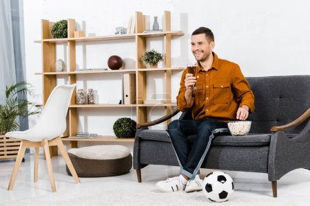 Photo for Handsome man in modern living room sitting on sofa while holding glass of beer and eating popcorn - Royalty Free Image