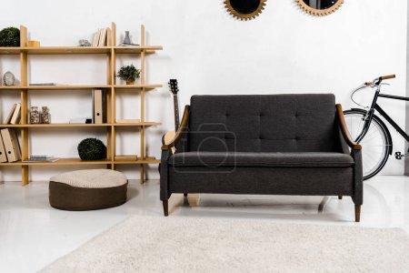 modernes Wohnzimmer mit Sofa, Akustikgitarre, Regalen und Pflanzen