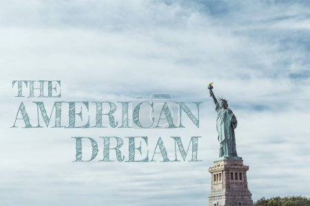"Photo for STATUE OF LIBERTY, NEW YORK, USA - OCTOBER 8, 2018: statue of liberty in new york against blue cloudy sky background with ""the american dream"" lettering, usa - Royalty Free Image"