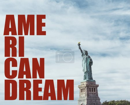 "Photo for STATUE OF LIBERTY, NEW YORK, USA - OCTOBER 8, 2018: statue of liberty in new york against blue cloudy sky background with ""american dream"" red lettering, usa - Royalty Free Image"