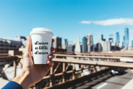 """Photo for Partial view of man holding disposable cup of coffee with """"dream a little dream"""" lettering and blurred new york city on background - Royalty Free Image"""