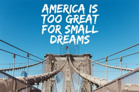 "Photo for Brooklyn bridge with american flag on clear blue sky background with ""america is too great for small dreams"" lettering, new york, usa - Royalty Free Image"
