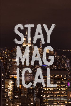 "aerial view of buildings and night city lights with ""stay magical"" lettering in new york, usa"