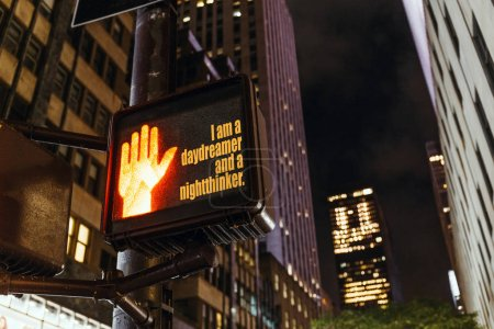 "Photo for Close up view of new york traffic light with ""i am a daydreamer and a nightthinker"" lettering, human hand sign and skyscrapers, usa - Royalty Free Image"
