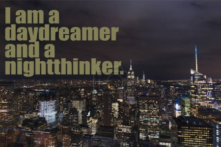 "Photo for Aerial view of buildings and night city lights with ""i am a daydreamer and a nightthinker"" lettering in new york, usa - Royalty Free Image"
