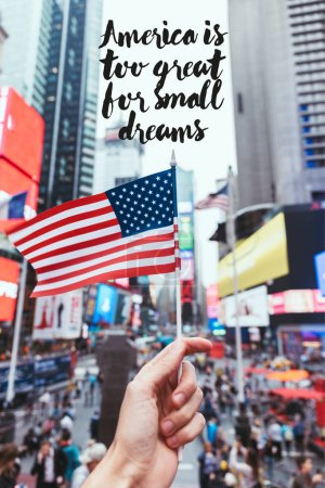 """partial view of man holding american flag on new york city street with """"america is too great for small dreams"""" quote"""