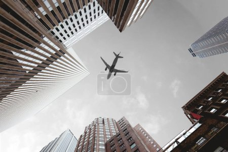 Photo for Bottom view of skyscrapers and airplane in cloudy sky in new york city, usa - Royalty Free Image