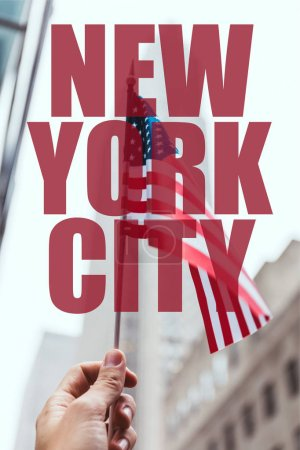 "cropped shot of man holding american flag in hand with blurred new york city street on background with ""new york city"" lettering"