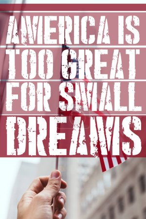 """Photo for Cropped shot of man holding american flag in hand with blurred new york city street on background and """"america is too great for small dreams"""" quote - Royalty Free Image"""