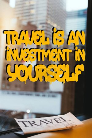 """close up view of travel newspaper with """"travel is an investment in yourself"""" quote on window and new york city on background"""