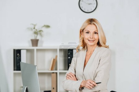 beautiful mature businesswoman standing with crossed arms and smiling at camera in office