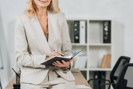 cropped shot of smiling blonde businesswoman sitting on table and writing in notepad at workplace