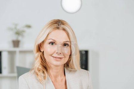 Photo pour Portrait de la belle femme mature blonde, souriant à la caméra dans le bureau - image libre de droit