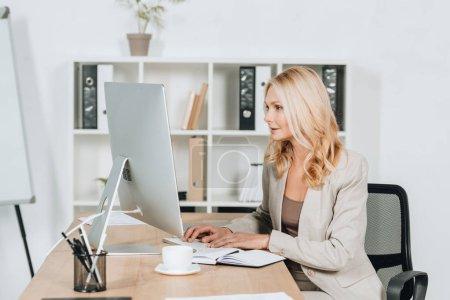 schöne professionelle Geschäftsfrau arbeitet mit Desktop-Computer im Büro