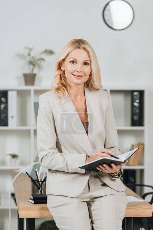 feliz madura empresaria escribiendo en bloc de notas y sonriendo a la cámara en la oficina