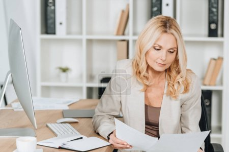 concentrated professional businesswoman sitting and working with papers in office