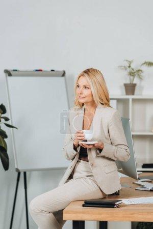 Photo pour Belle femme souriante tenant la tasse de café et assis sur la table au bureau - image libre de droit