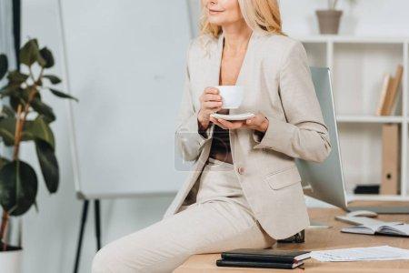 Photo pour Recadrée tir de femme souriante tenant la tasse de café et assis sur la table au bureau - image libre de droit